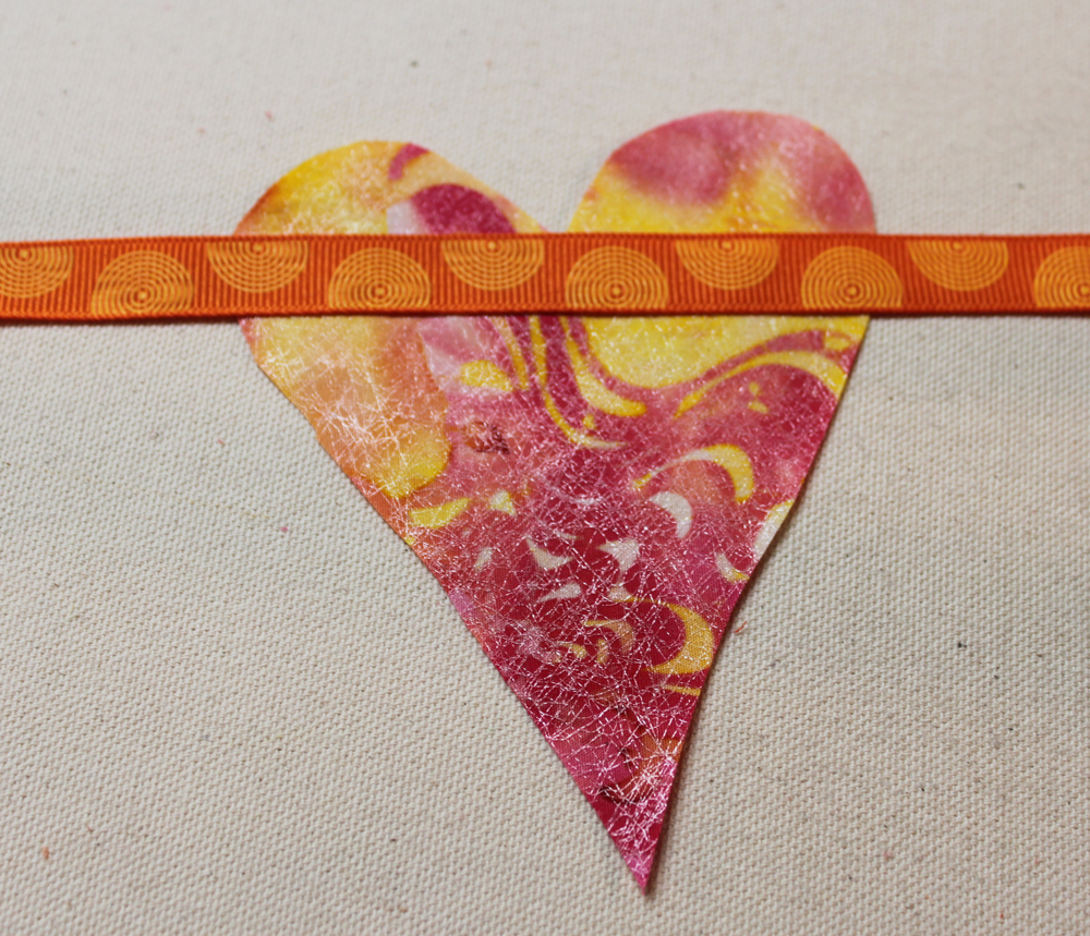 Place a heart on your ironing surface, fused side up. Place the ribbon across the heart leaving enough ribbon for tying in place.