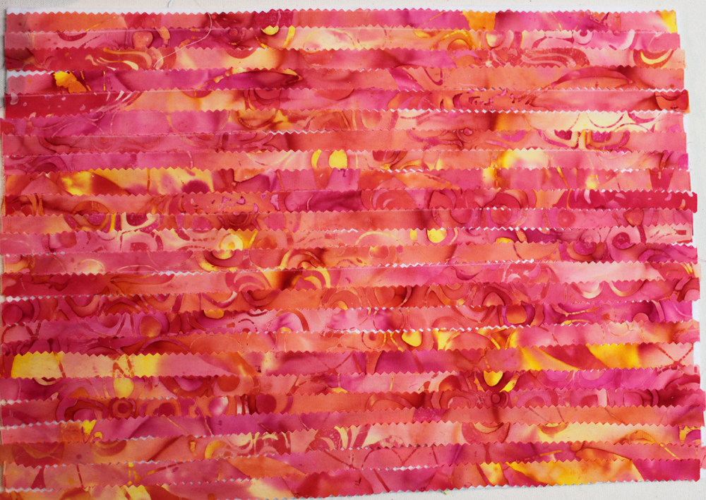 Place pinked strips of pink fabric directly on top of the misty fuse/felt in parallel rows.