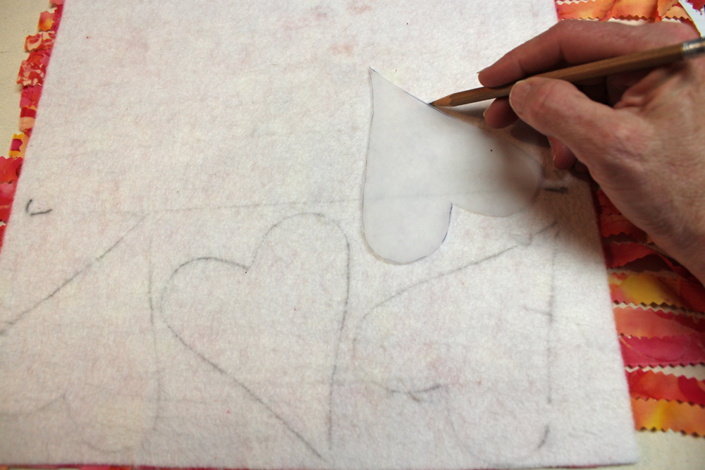 Make a heart template out of paper or plastic. Draw the template shape on the back of the felt.