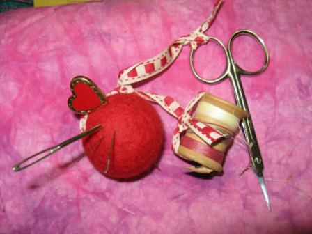 Tie your scissors to one end of ribbon and the spool to the other. Add some needles and use the hatpin to attach the heart shank button.