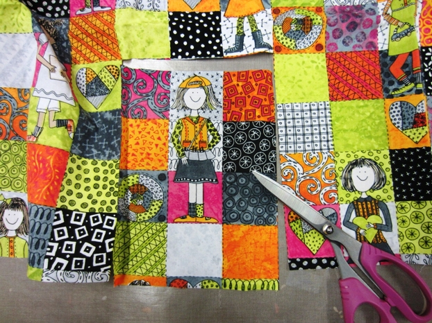"""Here is the girl fabric.  This has been pre-fused with Mistyfuse.  Each one of these squares is 2"""".  All of the artwork is from my drawings.  It is totally fun to see them come alive on fabric.  This is the perfect fabric for this project, because of the grid design."""