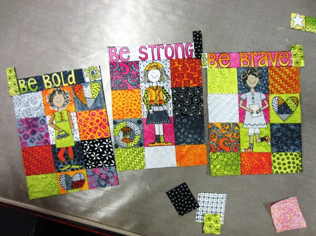"""Using some of the leftover 2"""" squares from the girl fabric and some of the artwork from the text fabric, select the words that you want, cut, and place them on the upper portion of the flag.  Press into place."""