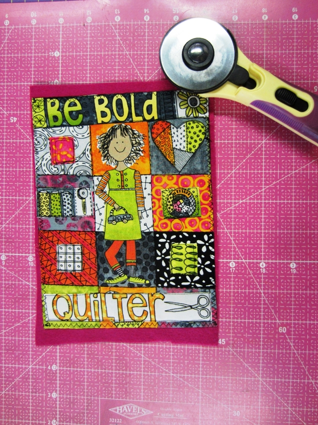 When you are finished free motion quilting all three pieces, trim the colored felt with a rotary cutter, ruler on a cutting mat.  You want to have a bit of it show through from the front.  It's a design element, and brings out the colors on your piece.